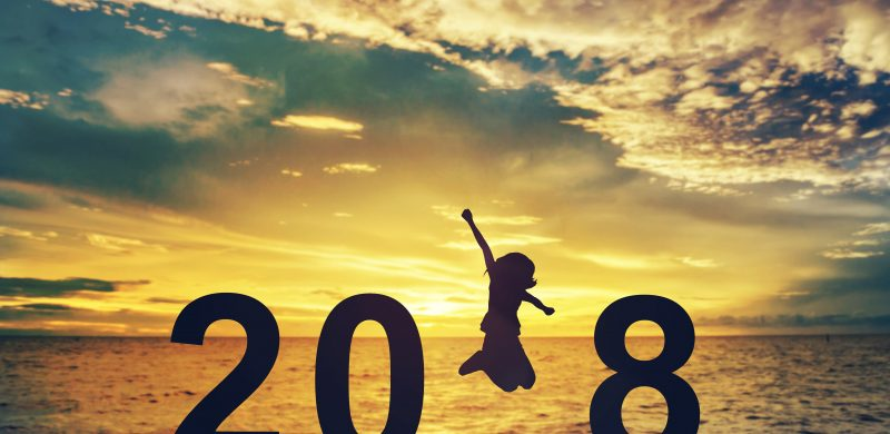 Silhouette young woman jumping on the sea and 2018 years while celebrating new year